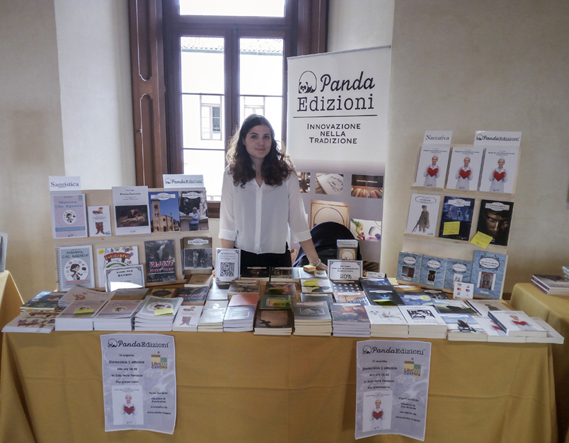 Editor Volpato (English-Italian-translator) standing behind a stand full of books during a bookfair.